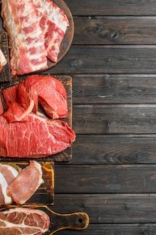 Rohes fleisch. verschiedene arten von schweine- und rindfleisch. auf einem holz.