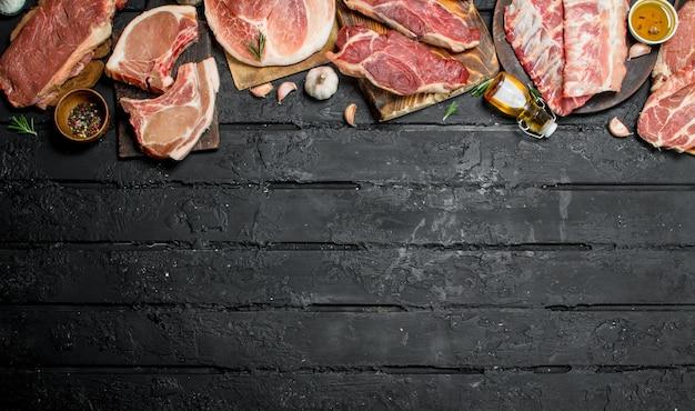 Rohes fleisch. verschiedene arten von schweine- und rindfleisch. auf einem schwarzen rustikalen hintergrund.