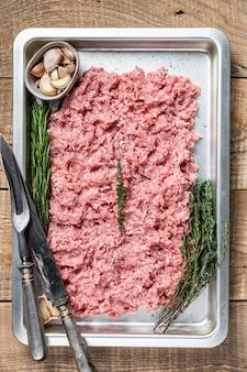Rohes fleisch von pute oder hühnerhackfleisch in einem küchentablett. holztisch. draufsicht.