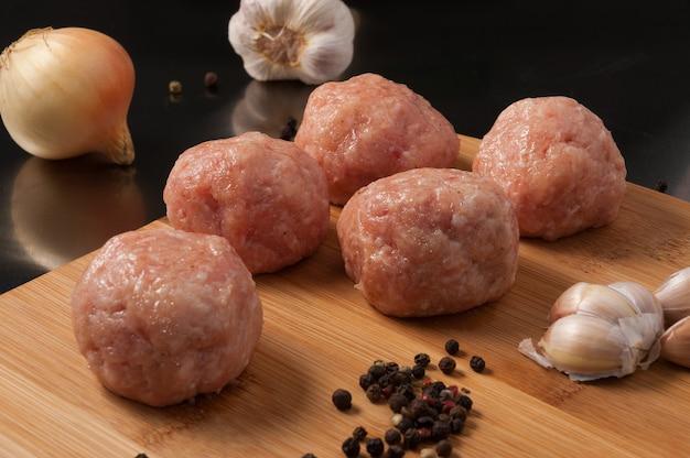 Rohes fleischbällchen huhn oder schwein auf holzbrett