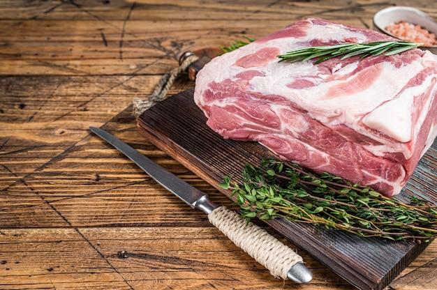 Rohes fleischstück mit schweinehalshals auf holzschneidebrett. hölzern