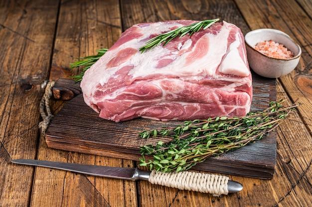 Rohes fleischstück mit schweinehalshals auf holzschneidebrett
