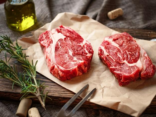 Rohes frisches chuck roll steak mit kräutern und salz auf einem schneidebrett