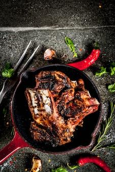Rohes frisches fleisch, geröstete oder gegrillte lamm- oder rindfleischrippen mit roter tomatensauce, peperoni, knoblauch und gewürzen in der pfanne
