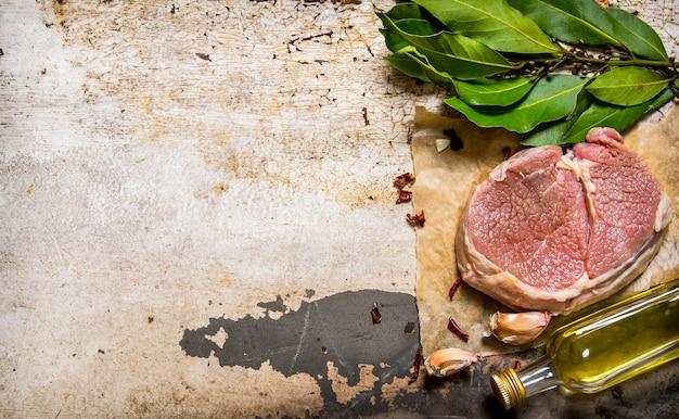 Rohes frisches fleisch mit knoblauch und öl auf einem holzbrett. auf rustikalem hintergrund. freier platz für text. draufsicht