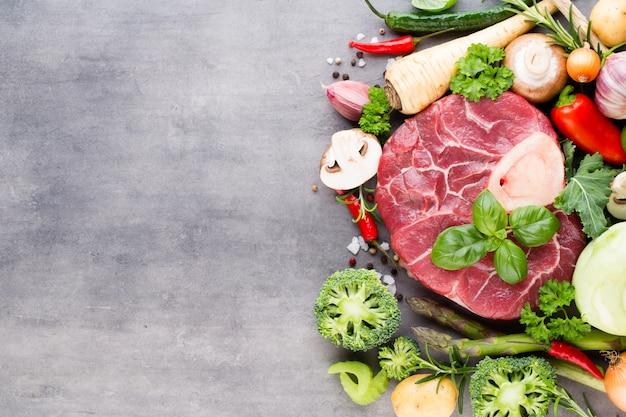 Rohes frisches fleisch ribeye steak mit gemüse und gewürzen.
