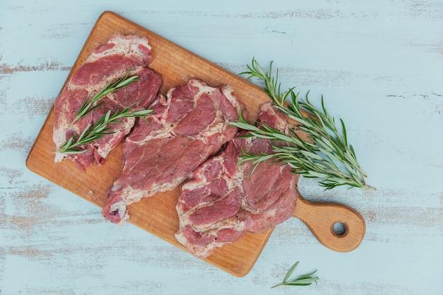 Rohes frisches fleischsteak entrecote, rosmarin und gewürze auf einem schneidebrett