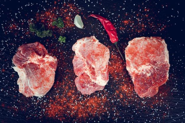 Rohes frisches gemarmortes fleisch steak und gewürze auf dunklem hintergrund