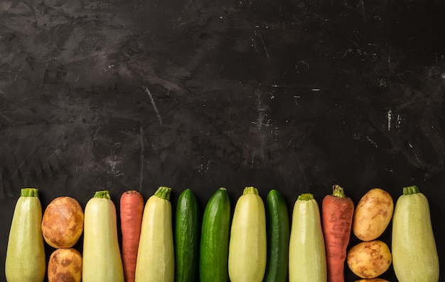 Rohes frisches gemüse auf dem schwarzen hintergrund in der linie in der draufsicht. zucchini, karotte, gurke und kartoffel
