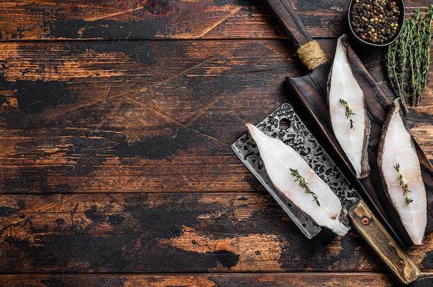 Rohes frisches heilbutt-fischsteak auf einem hölzernen schneidebrett.