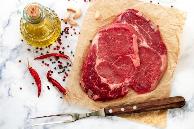 Rohes frisches organisches gemarmortes fleisch, rindfleisch, seesalz, pfeffer und knoblauch auf dem tisch, rib-eye-steak