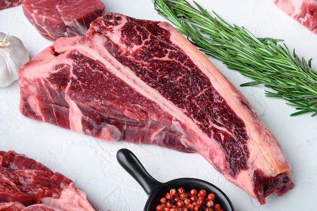 Rohes frisches rindfleisch-t-bone-steak-set, auf weißem steinhintergrund
