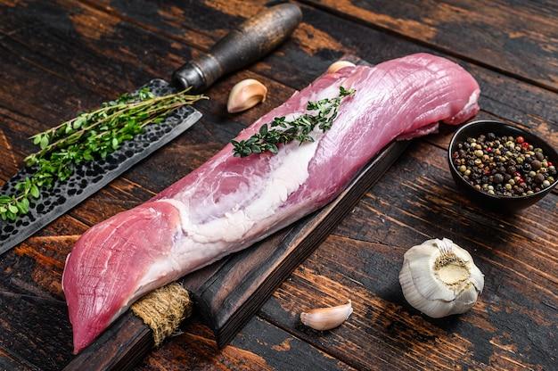 Rohes frisches schweinefiletfleisch auf einem schnittbrett mit hackmesser. dunkler hölzerner hintergrund. draufsicht.