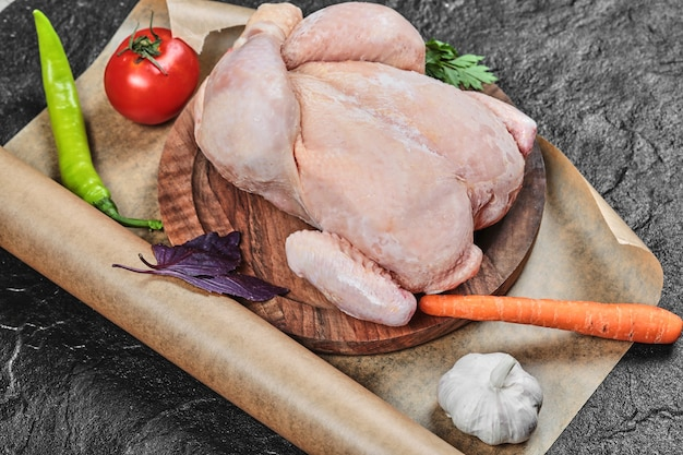 Rohes ganzes huhn auf holzteller mit frischem gemüse