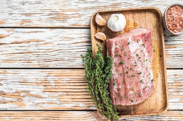 Rohes ganzes knochenloses schweinelendenfleisch mit thymian und salz auf rustikalem brett.