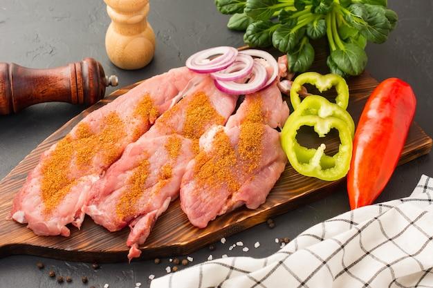 Rohes, gedämpftes schweinefilet bereit zum kochen mit gewürzen und kräutern auf dem schneidebrett.