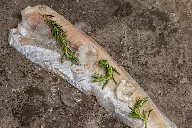 Rohes gefrorenes seehechtfilet mit eis, frischem rosmarin und trockenen zitronenscheiben.