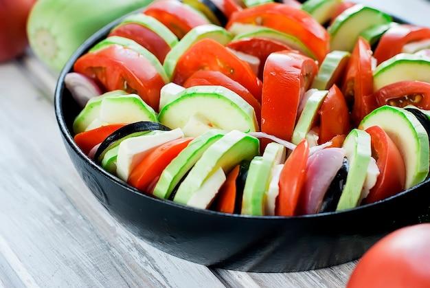 Rohes gemüse für ratatouille aus kürbis, tomaten und zwiebeln