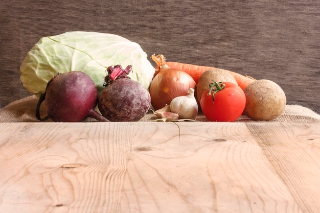 Rohes gemüse für rübensuppe borschtsch. weißkohl, rote rübe, karotte, kartoffel, tomate, knoblauch auf einem hölzernen brett
