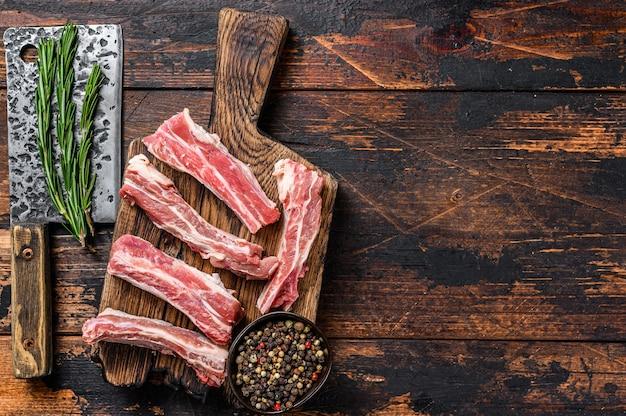 Rohes geschnittenes kalbfleisch kurze ersatzlendenrippen auf einem hölzernen schneidebrett