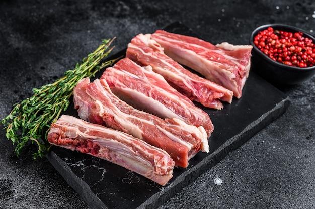 Rohes geschnittenes kalbfleisch kurze lendenrippen auf einem marmorbrett