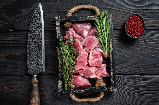 Rohes gewürfeltes schweinefleischjungenfleisch mit gewürzen in einem rustikalen tablett