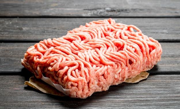 Rohes hackfleisch. auf einem hölzernen hintergrund.