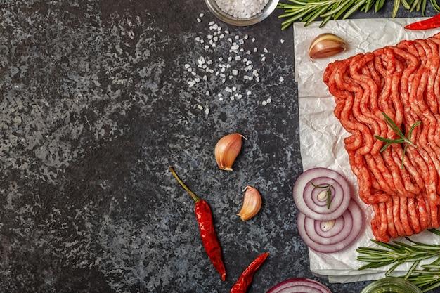 Rohes hackfleisch auf papier mit zwiebeln, kräutern und gewürzen auf bla