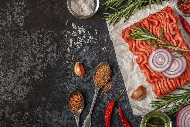 Rohes hackfleisch auf papier mit zwiebeln, kräutern und gewürzen auf schwarzer oberfläche