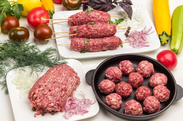 Rohes hackfleisch auf teller. rohe fleischbällchen in der pfanne. roher kebab auf holzspieß. gemüse und grüns auf dem tisch. weißer hintergrund.