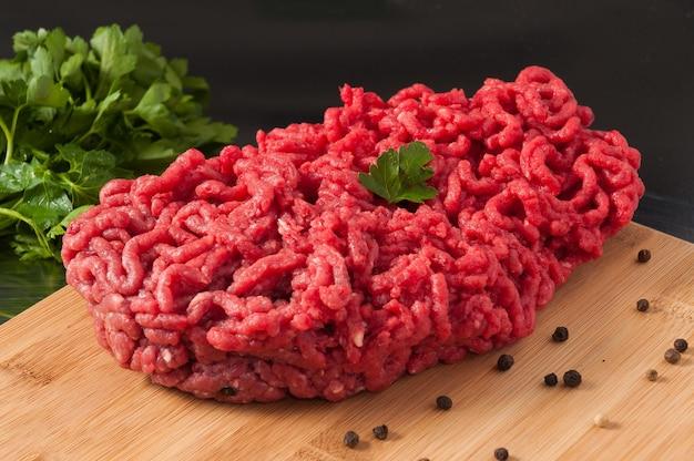 Rohes hackfleisch der schönheit verziert mit kräutern auf einem holzbrett