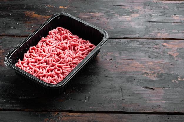 Rohes hackfleisch in einem schwarzen plastikbehälter, auf altem dunklem holztisch