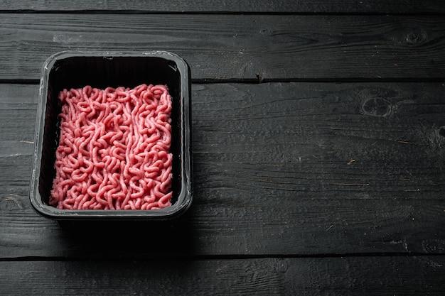 Rohes hackfleisch in einem schwarzen plastikbehälter auf schwarzem holztisch