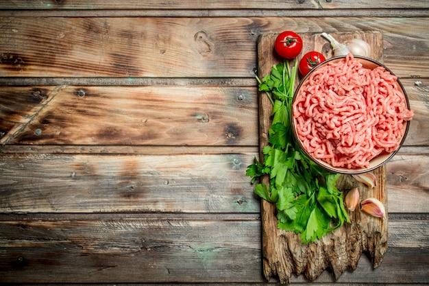 Rohes hackfleisch in einer schüssel mit petersilie, tomaten und knoblauch. auf einem hölzernen hintergrund.