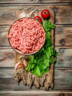 Rohes hackfleisch in einer schüssel mit petersilie, tomaten und knoblauch. auf einer holzoberfläche.