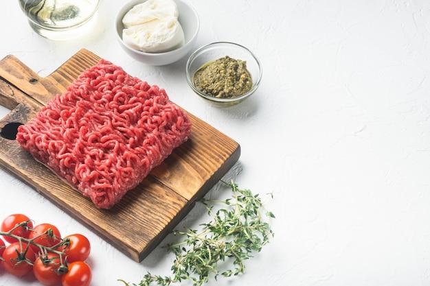 Rohes hackfleisch mit gewürzen, gemüse und kräutern und frikadellen, auf weißem stein white