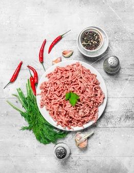 Rohes hackfleisch mit gewürzen und kräutern auf einem rustikalen tisch.