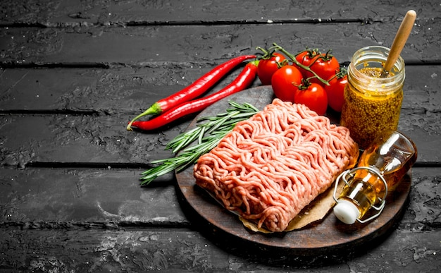 Rohes hackfleisch mit gewürzen und senfglas. auf schwarzem rustikalem hintergrund.