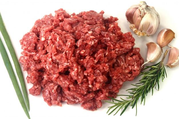 Rohes hackfleisch mit grünen blättern und gewürzen.