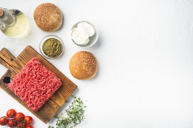 Rohes hackfleisch mit pfeffer, kräutern und gewürzen zum kochen fleischbällchen-burger-set, auf holzschneidebrett, auf weißem steintisch, draufsicht flach gelegt