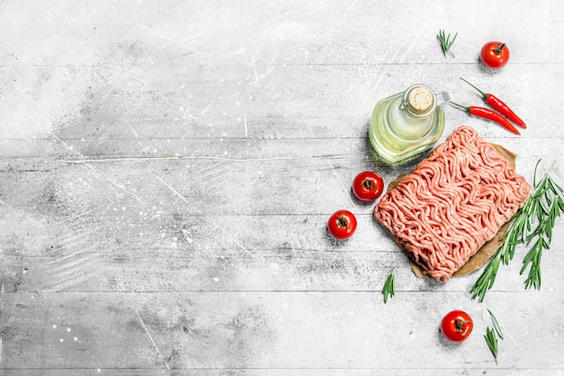 Rohes hackfleisch mit tomaten, rosmarin und gewürzen. auf einem rustikalen hintergrund