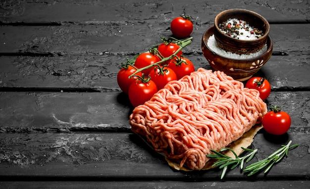 Rohes hackfleisch mit tomaten und rosmarinzweigen. auf schwarzem rustikalem hintergrund.