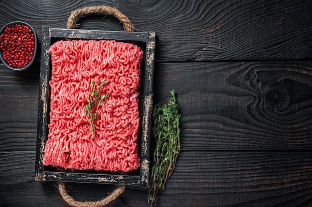 Rohes hackfleisch rind- und schweinefleisch in einem holztablett mit kräutern