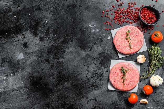 Rohes hackfleischschnitzel, rinderhackfleisch und schweinefleisch. burger pastetchen. schwarzer hintergrund. draufsicht. speicherplatz kopieren.