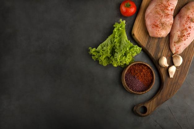 Rohes hähnchenfilet serviert mit grün und saucen