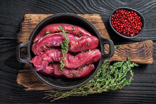 Rohes hammelfilet filetfleisch, lammfilet in rustikaler pfanne mit thymian. schwarzer holztisch. draufsicht.