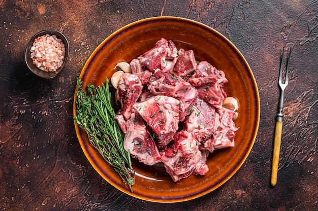 Rohes hammelfleisch gewürfelt für gulasch oder eintopf mit knochen auf einem rustikalen teller