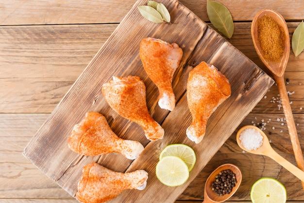 Rohes hühnchen. hühnerbeine auf einem schneidebrett vor dem hintergrund eines holztisches. fleischhühnchenzutaten zum kochen. flach liegen. ansicht von oben.