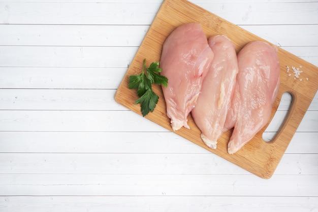 Rohes hühnerbrustfilet, rohes hühnerfleisch auf einem schneidebrett. weißer hintergrund, platz kopieren.