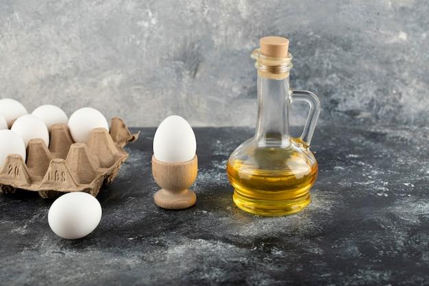Rohes hühnerei in eierbecher mit eierkasten auf einer marmoroberfläche.